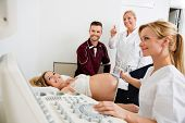 Young doctor checking pregnant woman while colleague and man looking at ultrasound machine