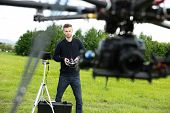 Young male engineer flying  UAV helicopter with remote control in park