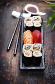 image of plate fish food  - sushi with chopsticks on wooden background - JPG