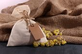 image of sachets  - Textile sachet pouch with dried flowers on wooden table - JPG
