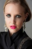 Portrait of beautiful blond woman with studio pulled back wearing diamante statement earrings and bl