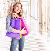 Excited woman with shopping bags in the mall, buying presents, happy consumer, spending money in fas