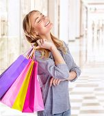 Woman having fun in shopping mall, smiling girl with closed eyes holding in hands colorful paper bag