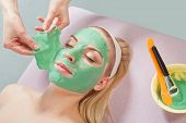 Young beautiful girl receiving facial green mask in spa beauty salon