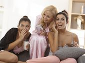Three girls in pyjamas at home listening as one talking to boyfriend, smiling elfish.