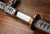 Katana, japanese sword, on wood background