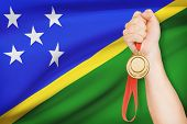 Medal In Hand With Flag On Background - Solomon Islands