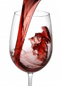 Red wine pouring into wine glass on white background