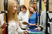 female student in library smiling and giving colleagues book