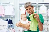 man father choosing shirt with daughter little baby girl during shopping at garments shop