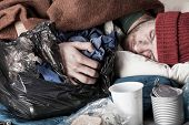 stock photo of homeless  - Homeless young man sleeping on the street - JPG