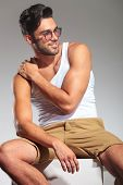 side view of a sexy seated man with hand on shoulder looking away to his side