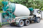Concrete Mixer Truck With Green Cab Over Trees