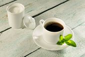Herbal sweetener stevia in powder form and a cup of coffee