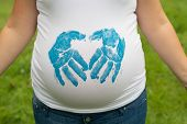 Pregnant Woman making hand-print in heart shape on her baby bump.