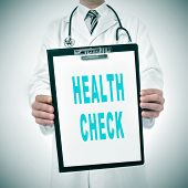 a doctor showing a clipboard with the text health check written in it