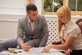 Young handsome architect discussing ground plan with client sitt