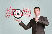 Business man hold audio speaker and music notes in hand