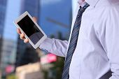Businessman Holding  And Using The Digital Tablet. Modern City Behind
