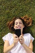 Top View Of A Woman Lying On The Grass Texting On A Smart Phone
