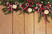 Christmas border with red and gold bauble decorations, holly and cedar cypress with pine cones over