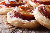foto of patty-cake  - Cakes of puff pastry with plums macro on an old table - JPG