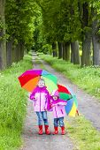 little girls wearing rubber boots with umbrellas in spring alley