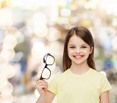 education, school and vision concept - smiling cute little girl holding black eyeglasses