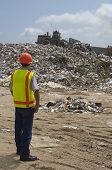 Worker watching digger moving waste at landfill site