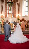foto of unity candle  - Bride and groom kneeling on wedding ceremony in front of altar - JPG