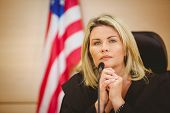 Portrait of a serious judge with american flag behind her in the court room