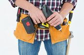Cropped image of male repairman holding drill machine over white background