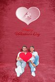 Cute couple sitting holding red heart against red