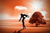 Ballet partners dancing gracefully together against sunny brown landscape