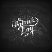 stock photo of saint patrick  - vector chalk typographical illustration of handwritten Saint Patricks Day label with light rays on the blackboard background - JPG