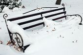 Bench in park with snowfall background
