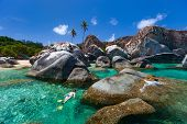 stock photo of virginity  - Young woman snorkeling in turquoise tropical water among huge granite boulders at The Baths beach area major tourist attraction on Virgin Gorda - JPG