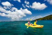 Mother and son paddling on colorful yellow kayak at tropical ocean water during summer vacation