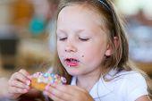 Adorable little girl enjoying eating donut at cafe