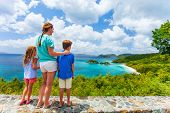 Family of mother and kids enjoying aerial view of picturesque Trunk bay on St John island, US Virgin Islands considered by many as most beautiful beach in Caribbean