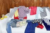 Messy clothing on white sofa, on wooden planks  background