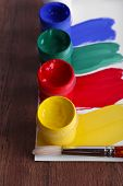 Colorful paint strokes with brush and paint cans on white sheet of paper on wooden table background