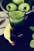 Spinach drink and apples on a wooden table