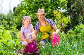 Mother and daughter gardening in garden