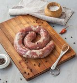 Ring Of Raw Sausage On A Cutting Board With Pepper