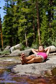 Hiking girl relaxing sleeping in nature next to river creek. Tired hiker resting lying down outdoors taking a break from hike. Young Asian woman in forest in Yosemite national park, California, USA.