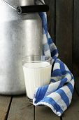 Retro can for milk with colorful towel on color wooden background