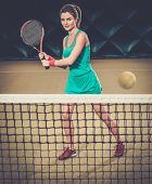 Young woman playing tennis indoors