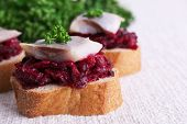 Rye toasts with herring and beets on tablecloth background