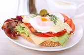 Sandwich with poached egg, tomato and bacon on plate on wooden background